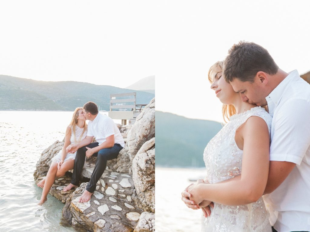 Bride and groom sit kissing on the rocks at San Nicolas Resort during their honeymoon photography session