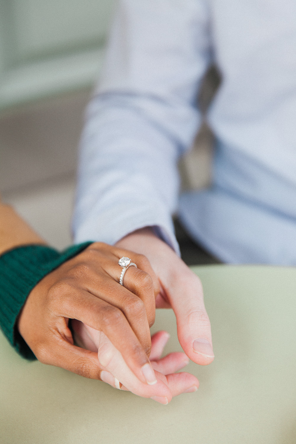 Couple holding hands showing off the brides diamond Tiffany engagement ring