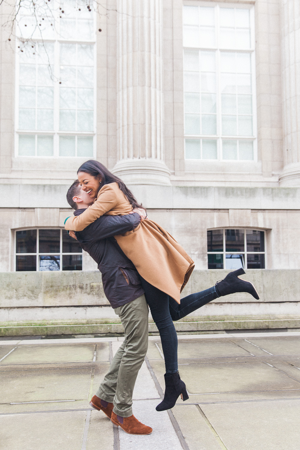 Groom lifting bride during their engagement shoot in London