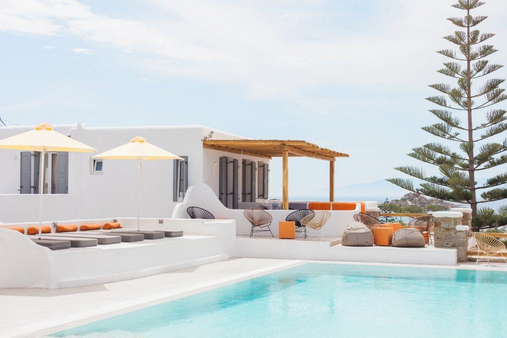 The pool area at Artemoulas Studios Mykonos with yellow umbrellas and orange towels