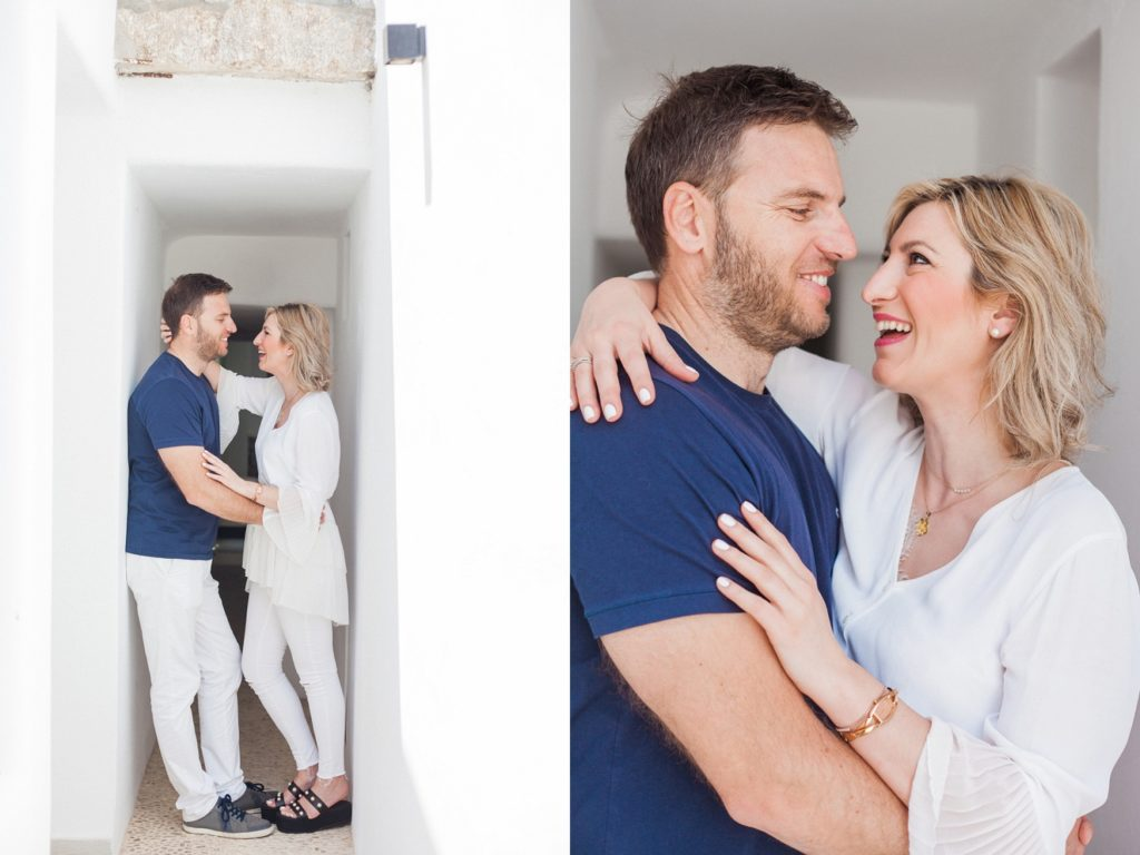 Greek couple share a laugh in a whitewashed corridor on Mykonos island