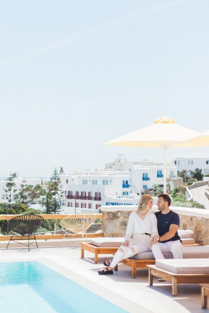 Couple sit together under a yellow umbrella at Artemoulas Studios Mykonos