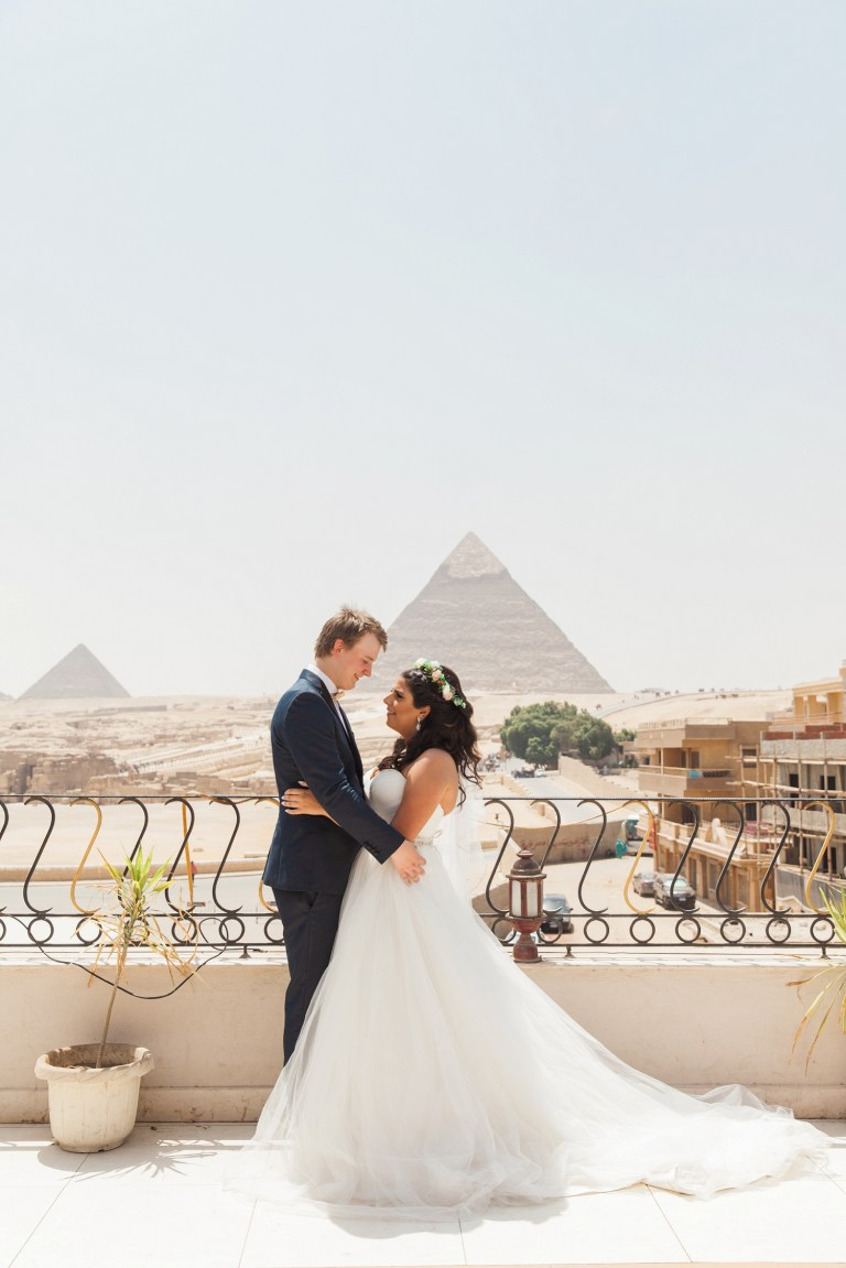 Bride and groom stand together in front of the Great Pyramids of Giza during their Egypt wedding in Cairo
