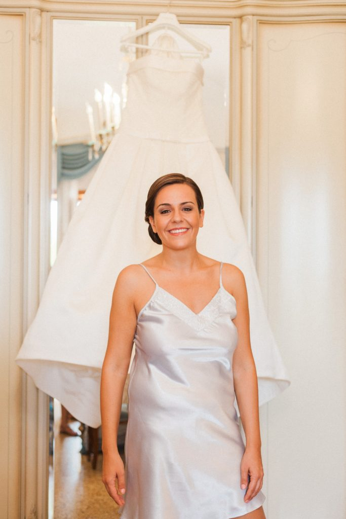 Italian bride smiles as she stands in front of her Pronovias gown