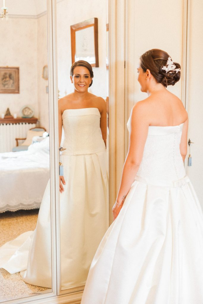 Bride smiles as she looks at herself in the mirror on her wedding morning