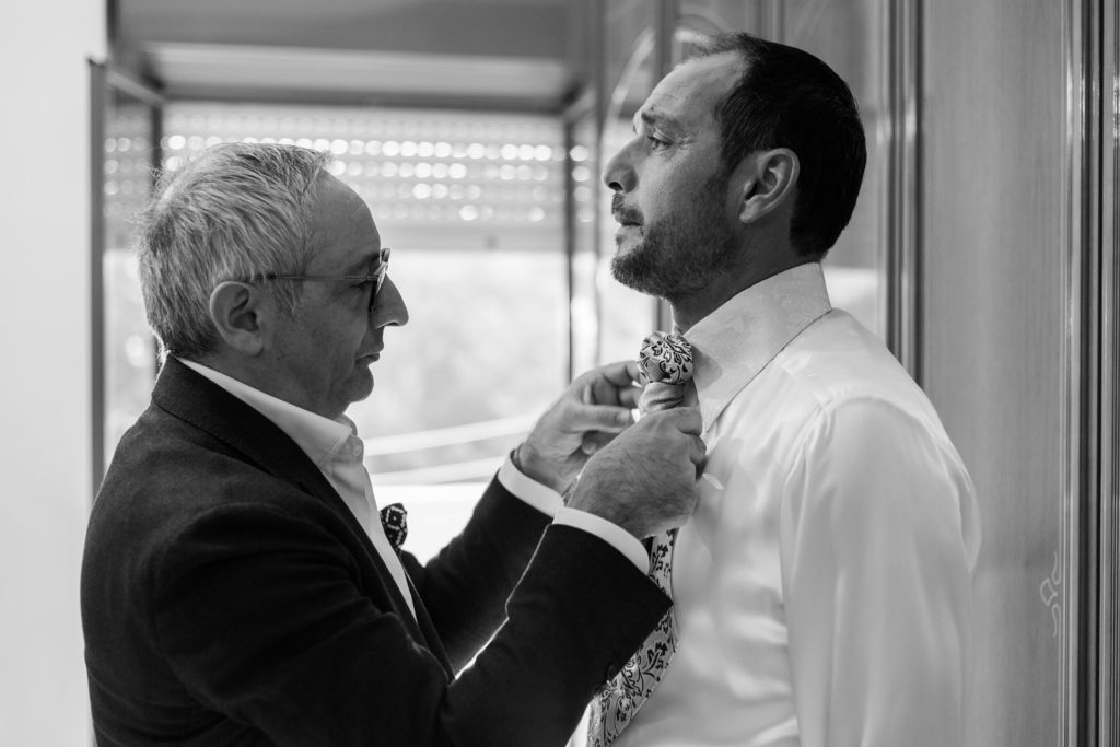 The groom is helped with his tie by a friend on the morning of his wedding