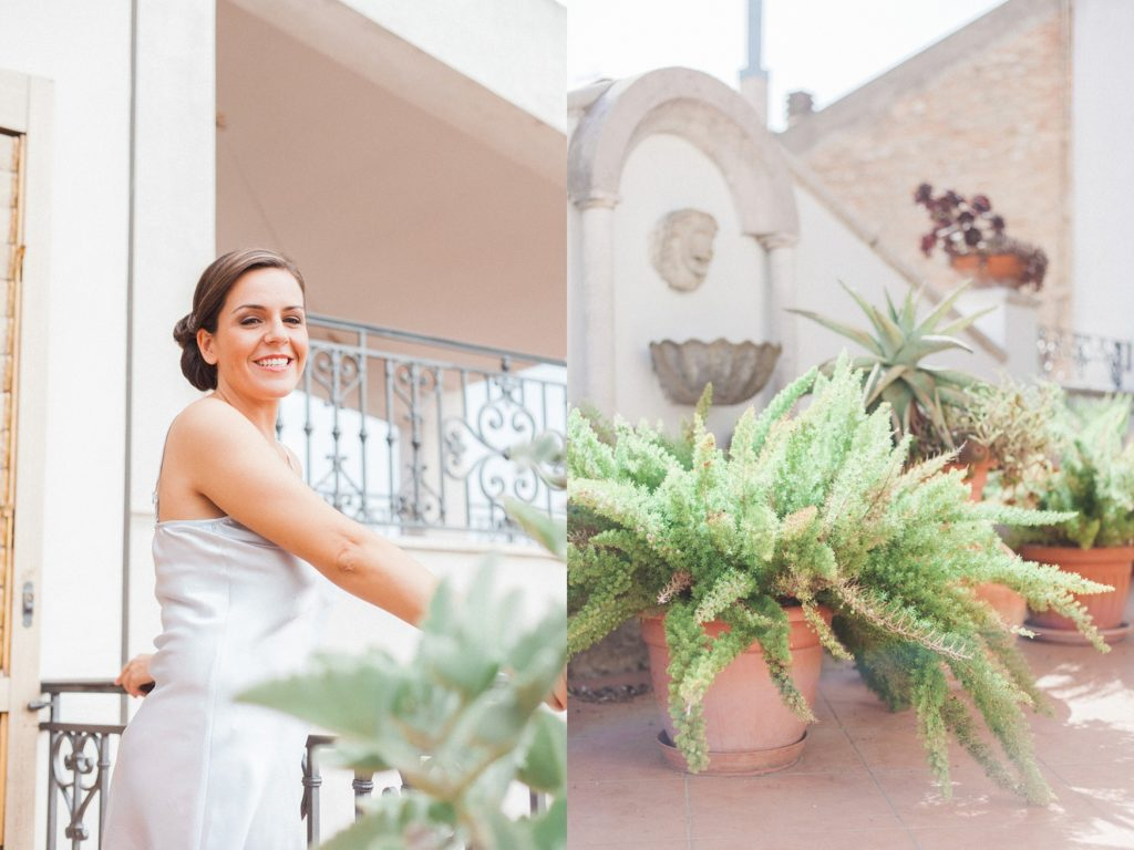 Italian bride stands on the balcony of her parents house in the sunshine on the morning of her Abruzzo wedding