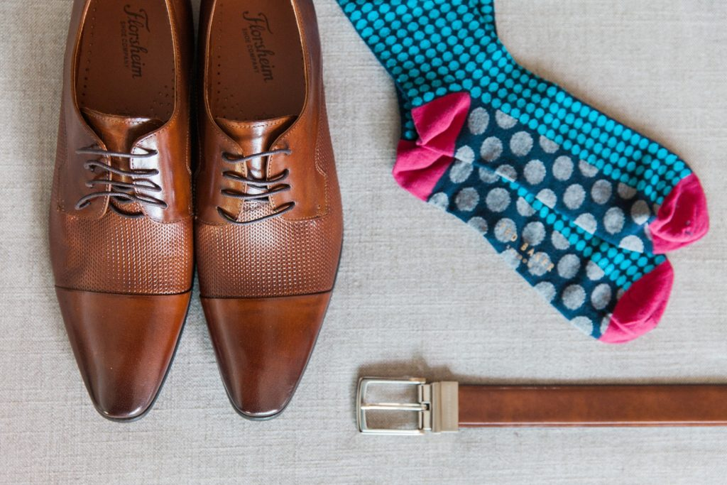 Flat lay of the grooms details including shoes, socks and a belt