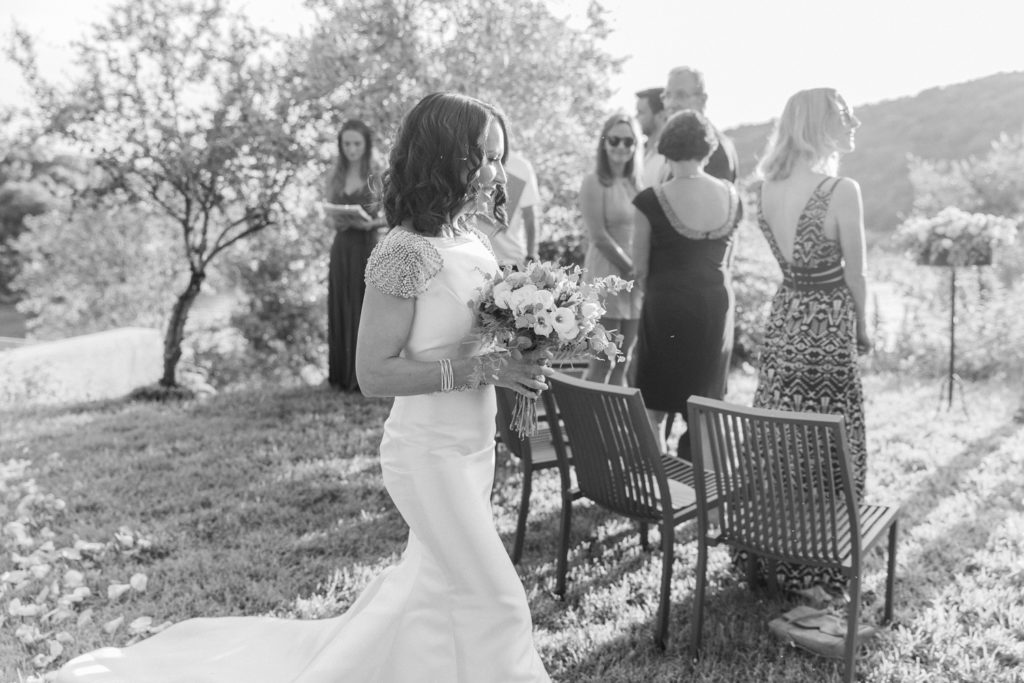 Guests clap as bride arrives at her wedding ceremony at Domotel Agios Nikolaos in Sivota