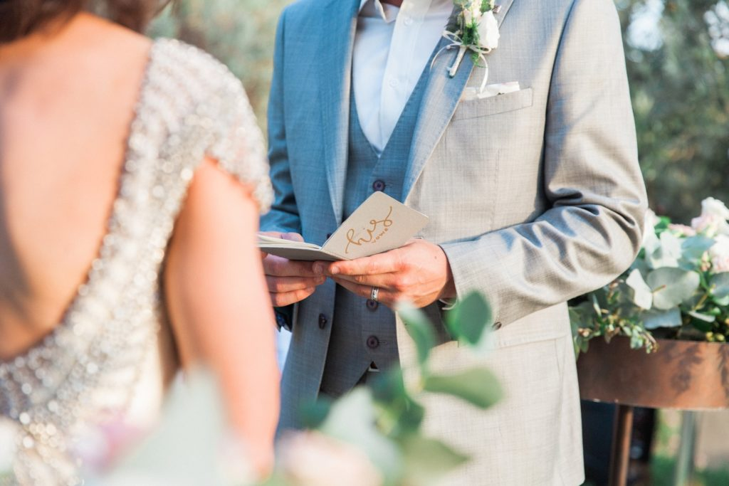 Close up of a grooms vow book during his wedding ceremony