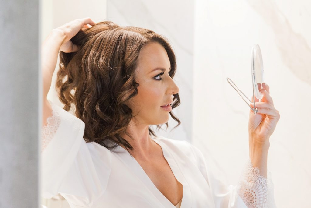 Bride checking her make-up and hair in a hand held mirror on her wedding day