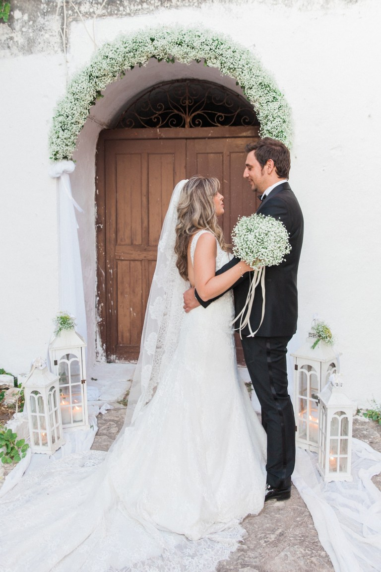 Bride and groom smile at each other outside the church door in Santa Maura Castle in Lefkada
