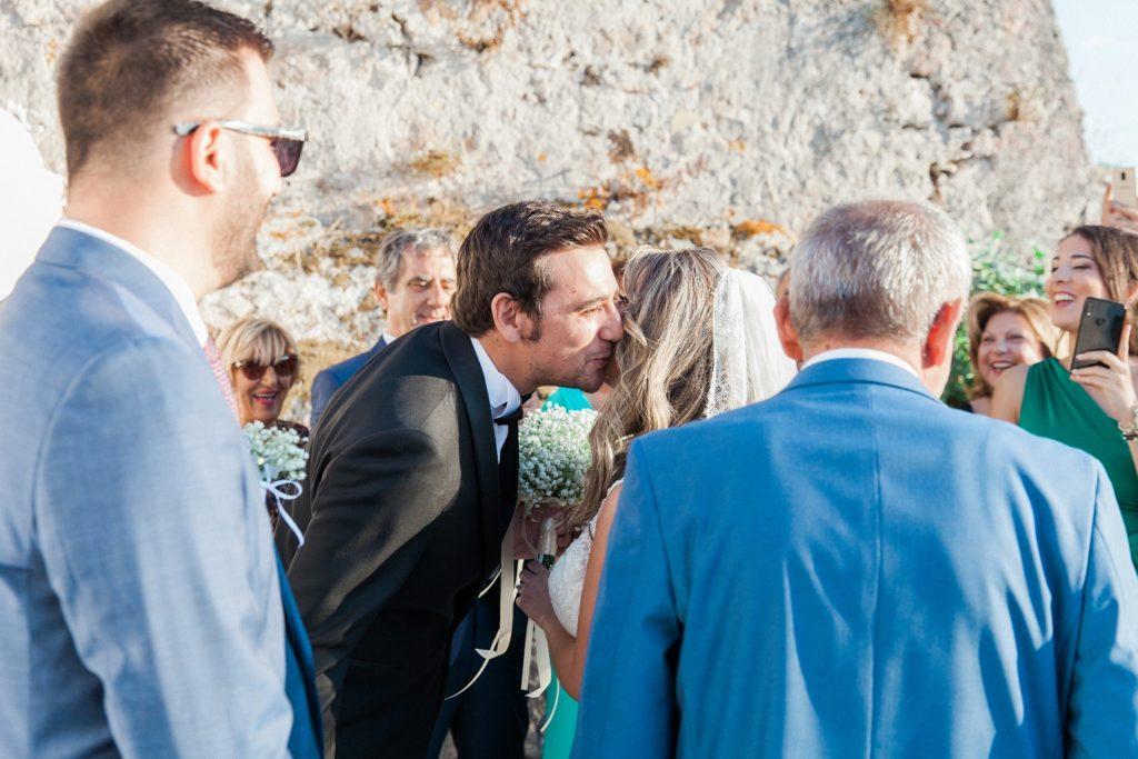 Groom kisses the bride as she arrives at the church inside Santa Maura Castle