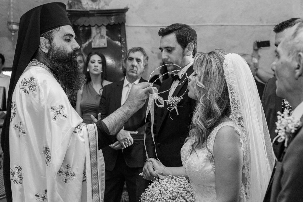Bride kisses the stefana or Greek wedding crowns during her ceremony in Santa Maura Castle