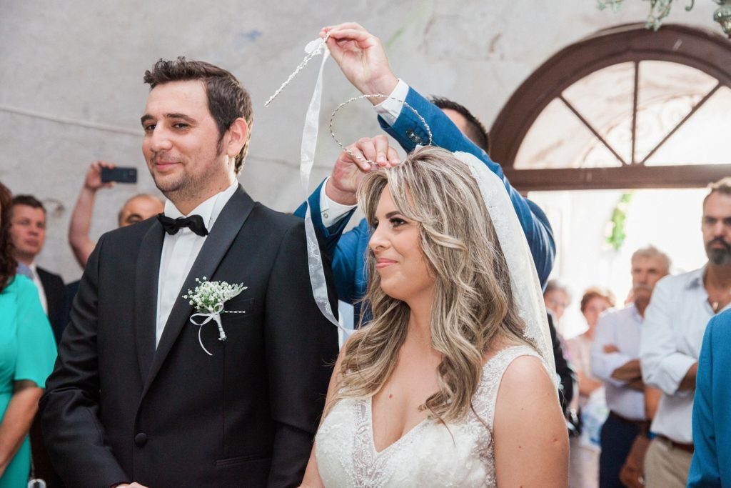 Best man moves the wedding crowns or stefana between the bride and grooms heads during the Greek wedding ceremony