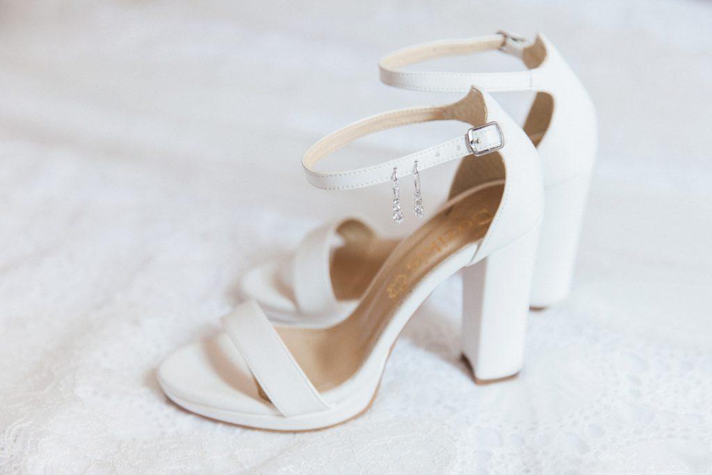 Brides heels with diamond earrings on handmade lace