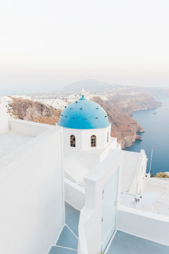 A blue and white Greek church with the cliffs of Santorini in the background