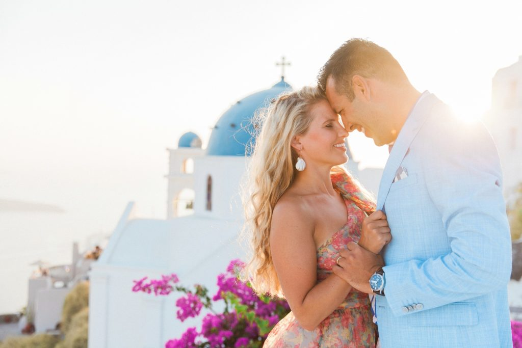 Couple share an intimate moment on a Santorini rooftop at sunset