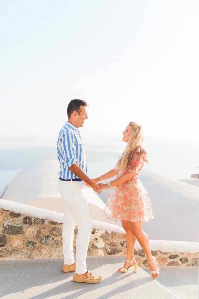 Happy couple hold hands during their honeymoon on Santorini