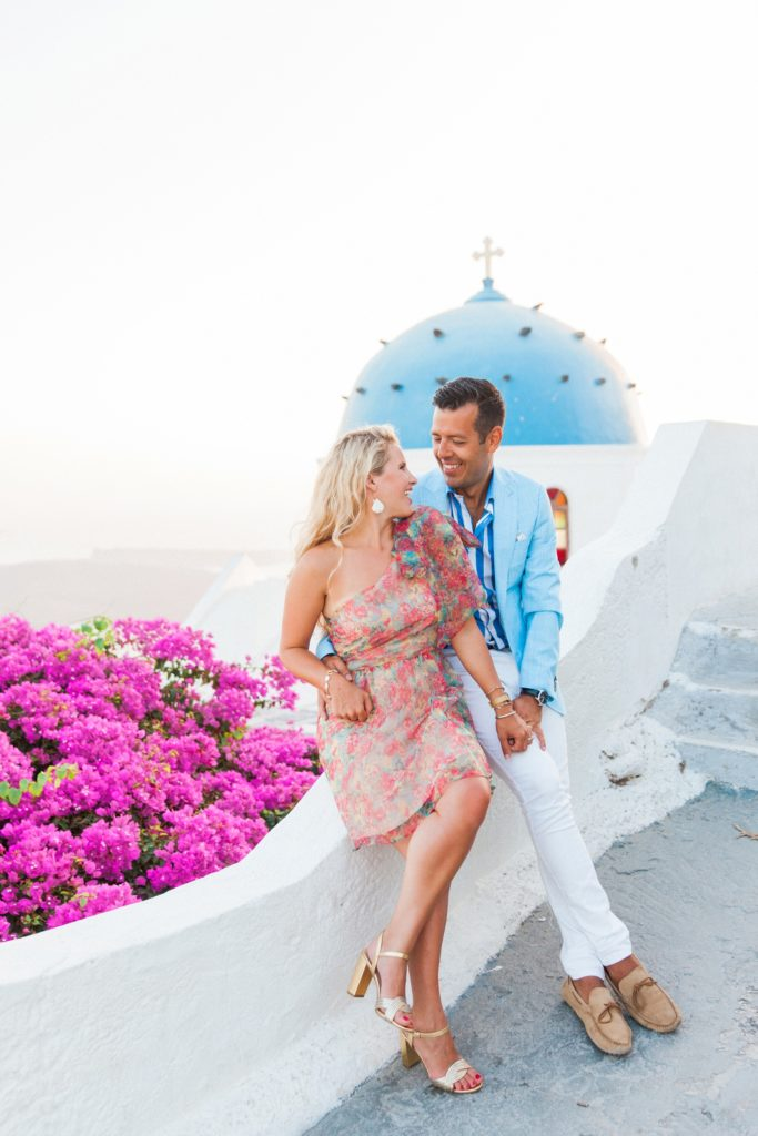 Couple sit together on a wall infront of a Greek church and pink bougainvillea in Santorini