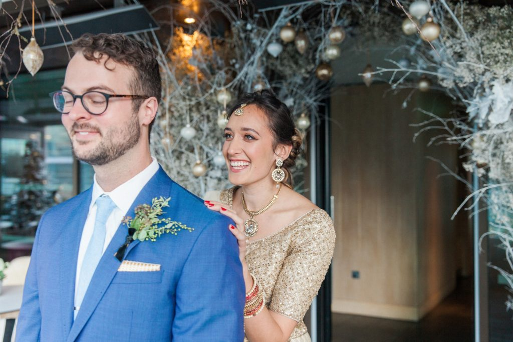 Bride smiles as she taps her groom on the shoulder during their first look