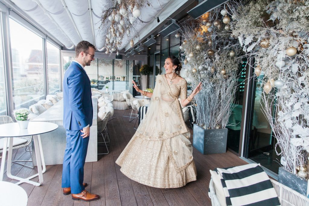 Indian bride shows off her wedding lehenga to her husband during their first look