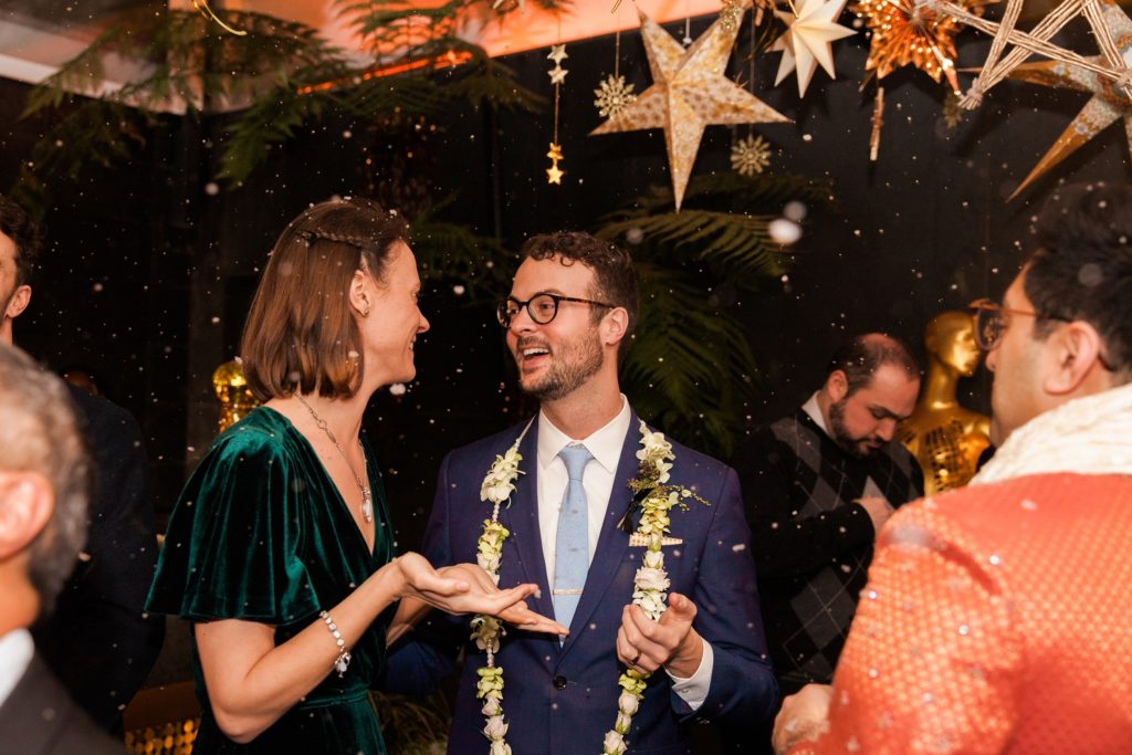 Groom and his sister smile under a fake snow fall in the Secret Garden bar at South Place Hotel