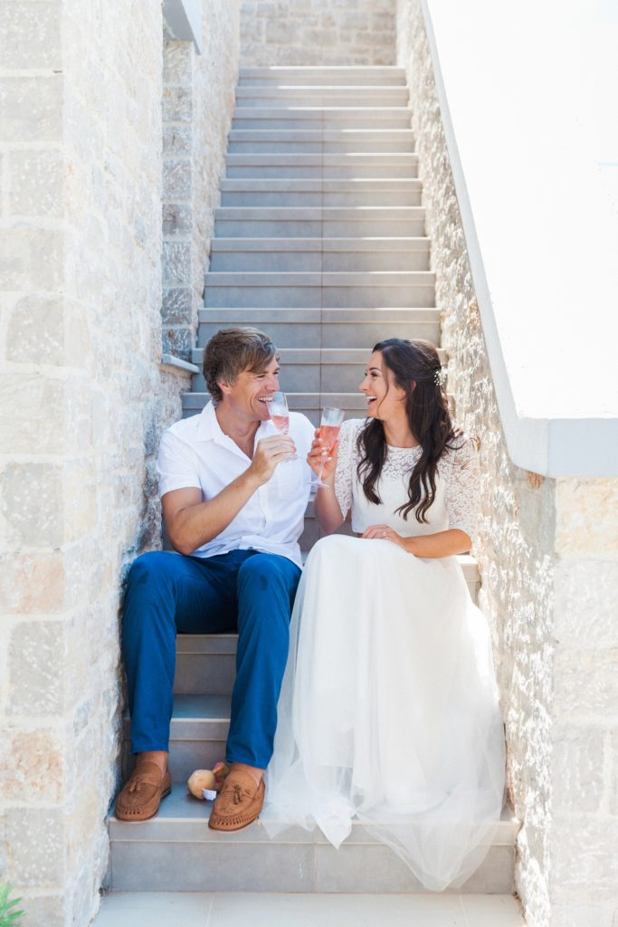 Bride and groom sitting on the steps of their villa toasting with pink prosecco after their elopement