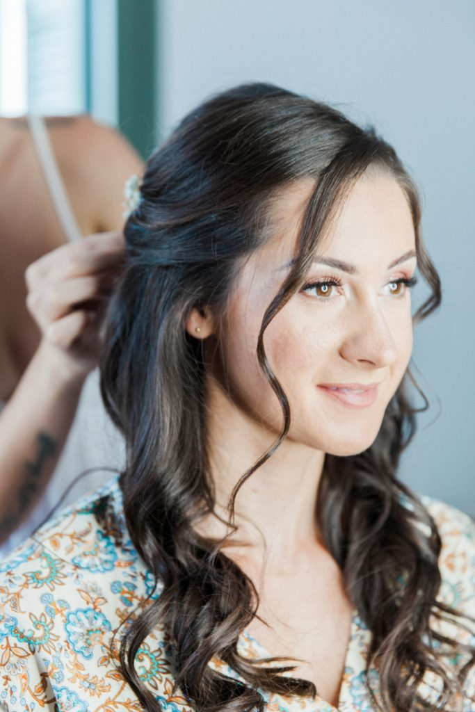 Bride smiles while she gets her hair done on the morning of her elopement
