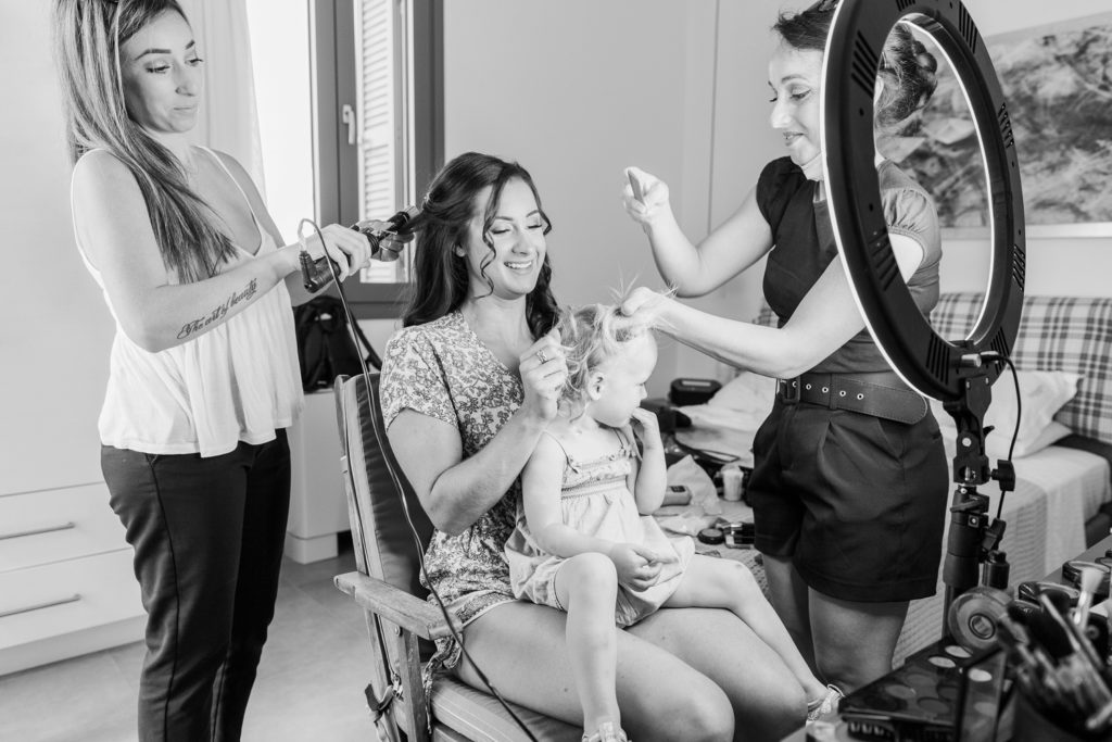 Bride and make-up artists work together to do flower girls hair