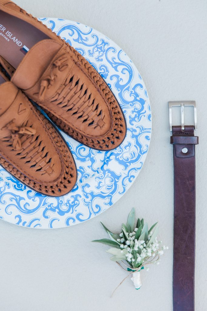 Flatlay of the grooms details including shoes, belt and buttonhole