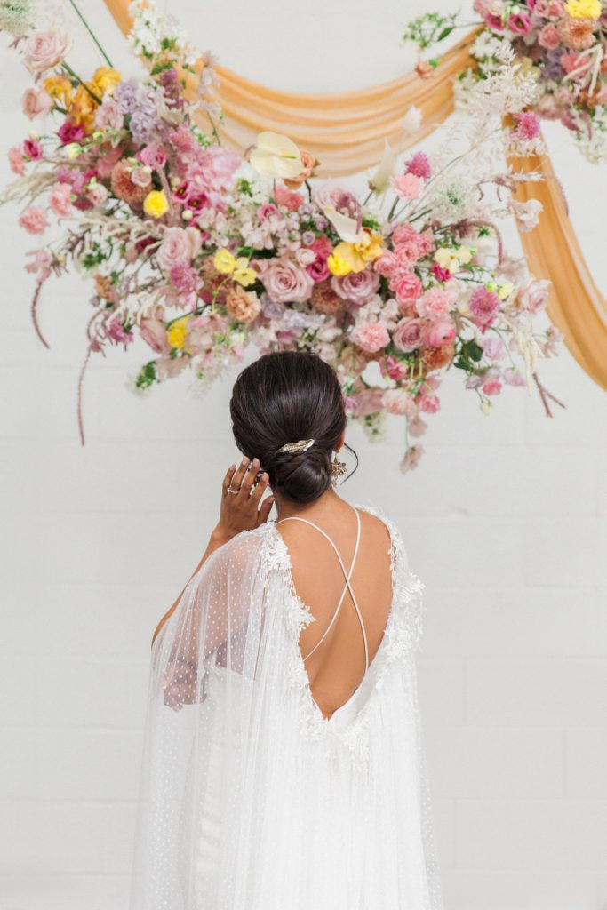 Bride stands under colourful hanging floral arrangements in a Halfpenny London wedding dress