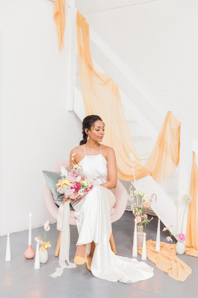 Beautiful black bride sitting in a pink lounge chair surrounded by colourful flowers and candles