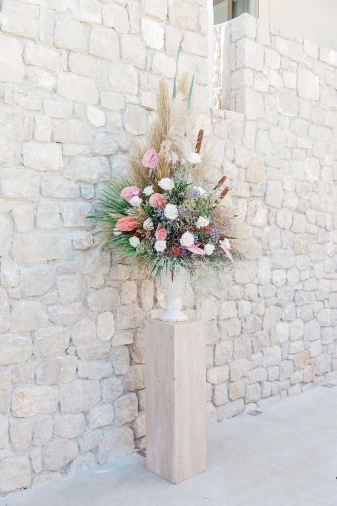 Pastel wedding flowers with bullrushes in a stone urn at Crystal Waters Lefkada