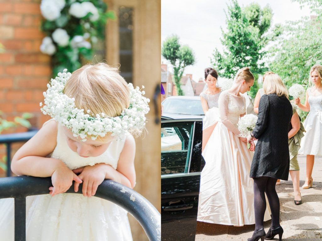 Flowergirl stands at the door of the church wearing a gypsophila crown while the bride gets out of the car