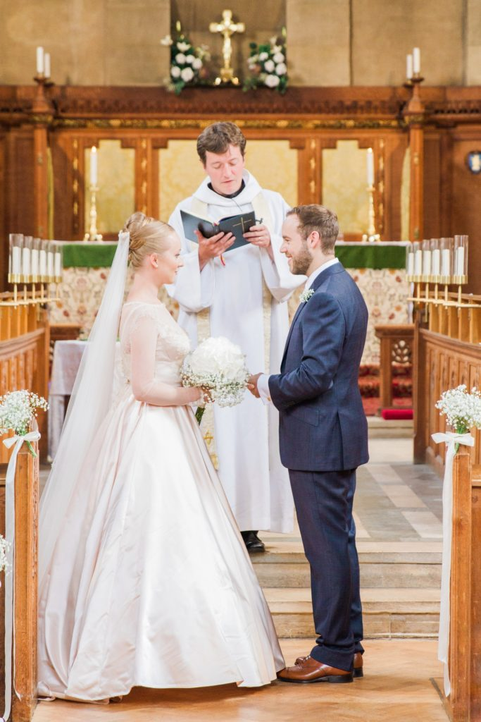 Bride and groom smiles at each other during their wedding ceremony in a traditional English church