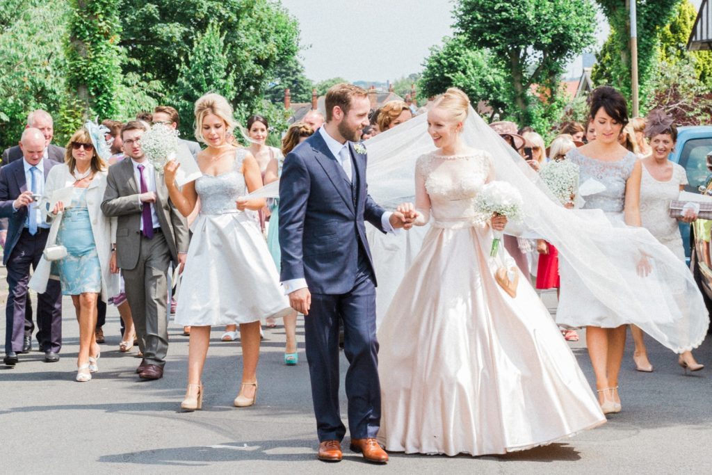 Newly married couple lead their guests from the church through the village to their English garden wedding reception