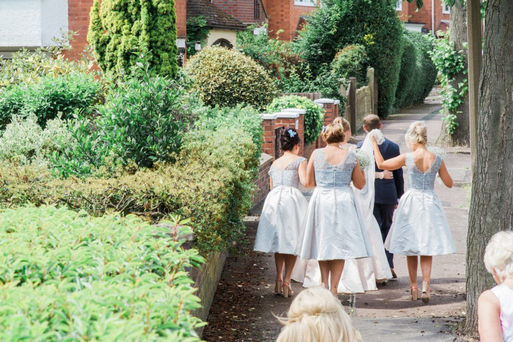 Bride and groom are followed through the streets of the village to their English garden wedding reception