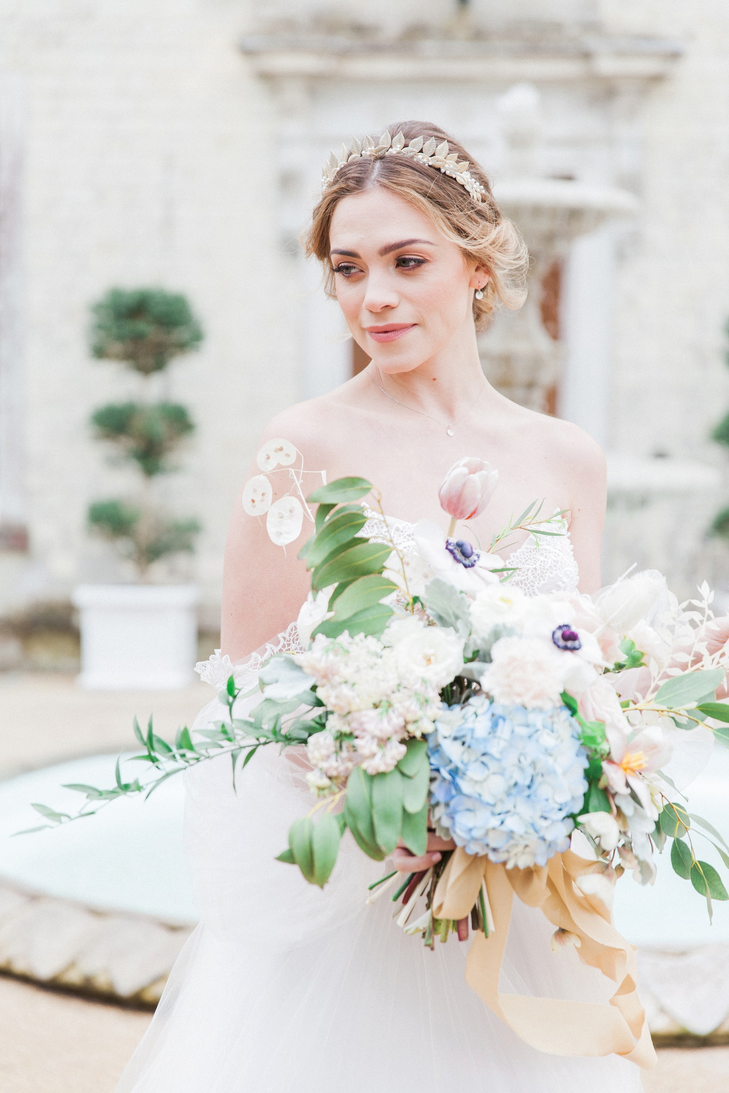 Bride holding a pastel bouquet in front of Froyle Park wedding venue