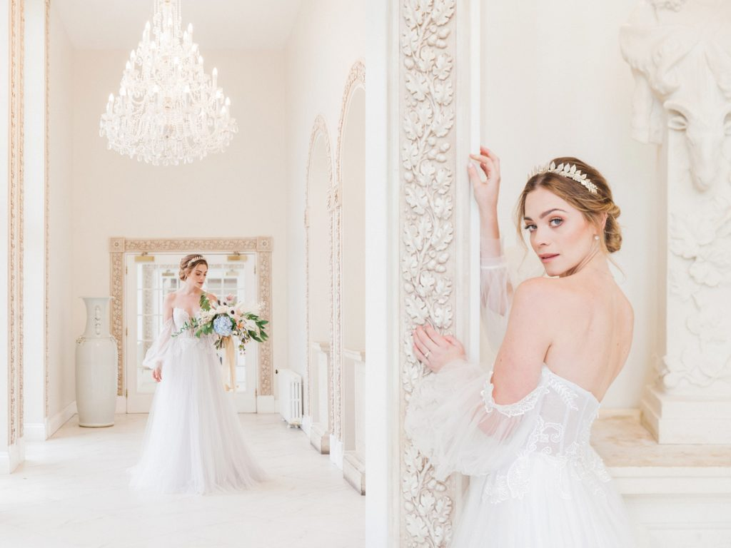 Bride in a Chic Nostalgia gown poses under a chandelier in a marble corridor