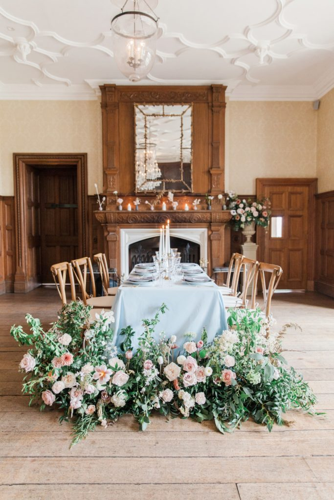 Beatrix Potter inspired wedding reception table with blue pastel tablecloth and wild flowers.