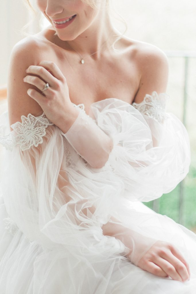 Bride shows off her grey diamond engagement ring by Lilia Nash Jewellery while wearing a gown by Chic Nostalgia