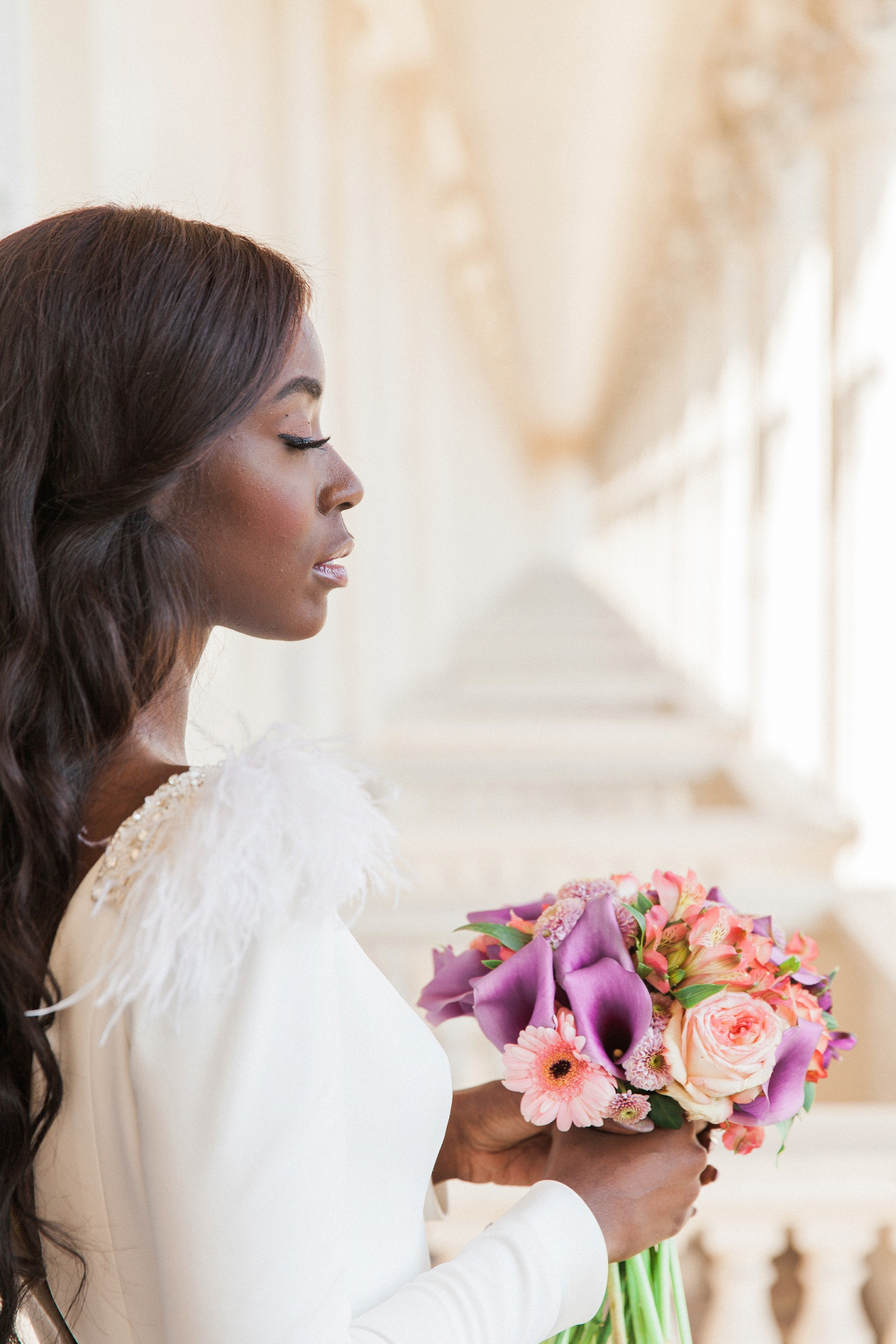 Beautiful black bride on a balcony in London holding a colourful bouquet