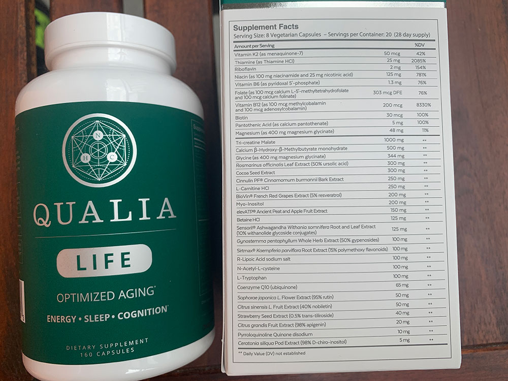 One bottle of Qualia Life next to the packaging box of Qualia Life which states the Supplement Facts and ingredients