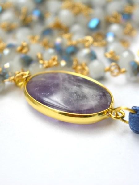 """SAUTOIR NOUR SERENITY """"BOHEMIENNE CHIC"""" - Sautoir en perles de cristal bleu gris nuancé, chaîne plaqué or, cabochon améthyste, pompon soyeux"""
