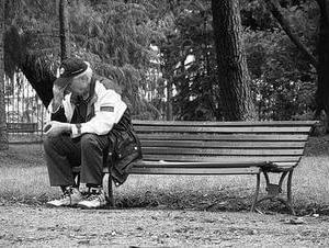 anciano sólo en el extremo de un banco
