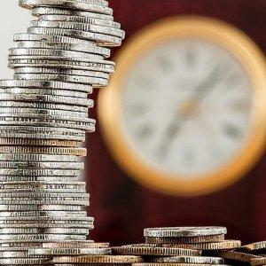 Imagen de una montaña de monedas junto a un reloj grande de pared
