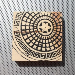 Copenhagen manhole cover artwork on wood block