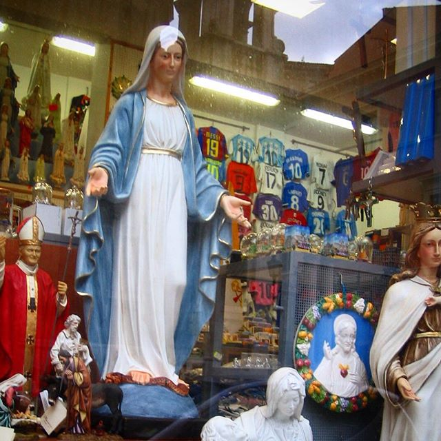 statues and soccer jerseys in rome, roman football strips, roma virgin mary, jesus mary and joseph, religious icons of italy, photography of store windows