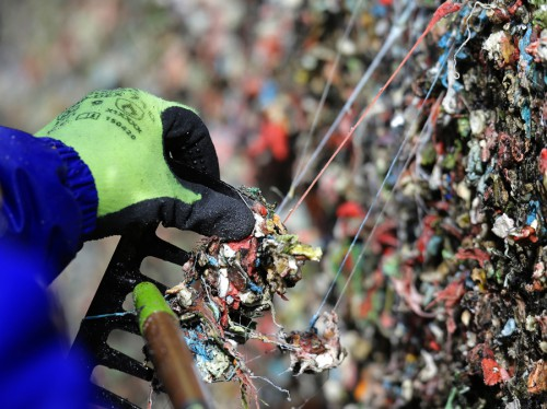 """Fernando Soberania uses a tool to scrape layers of gum from Seattle's famous """"gum wall"""" at Pike Place Market, Tuesday, Nov. 10, 2015. Tourists and locals have been sticking their used chewing gum on the walls of a section of Post Alley for the past 20 years, and although the walls will be cleaned down to bare brick, officials expect the gum-sticking tradition will quickly return. (AP Photo/Ted S. Warren)"""